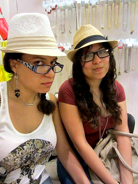 Two brunettes in fedoras make unamused faces at camera.
