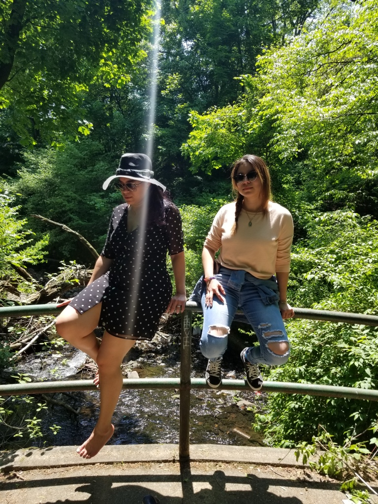 Two brunettes sit on a bridge railing, backlit by the noon sun.