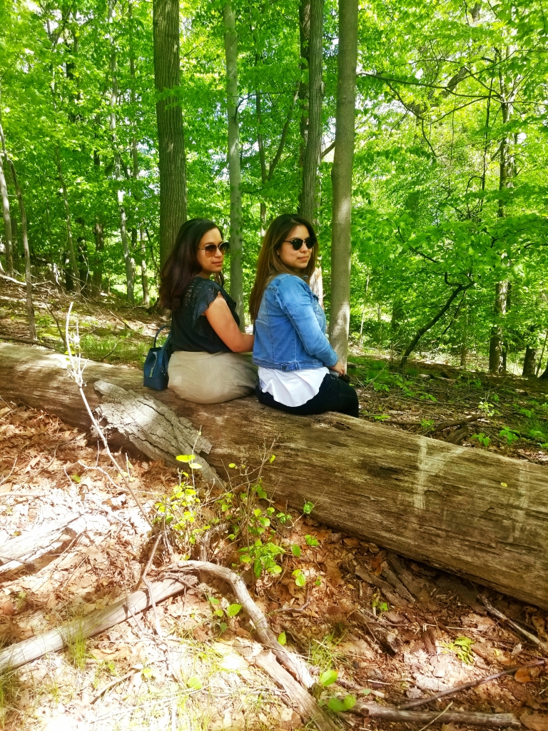 Two brunettes sit on fallen tree trunk, looking over their shoulders at the camera.