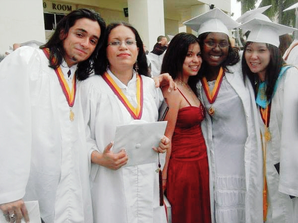 Four graduating high school seniors, three girls, one boy, pose in white caps and gowns. Junior girl in red dress joins them.