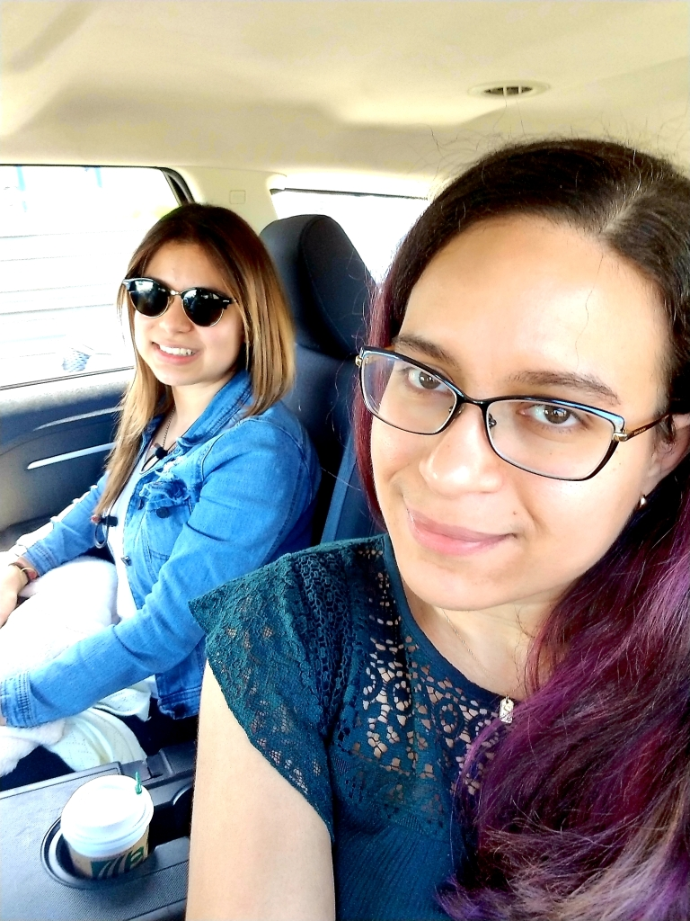 Two brunettes smile in the back of an Uber.