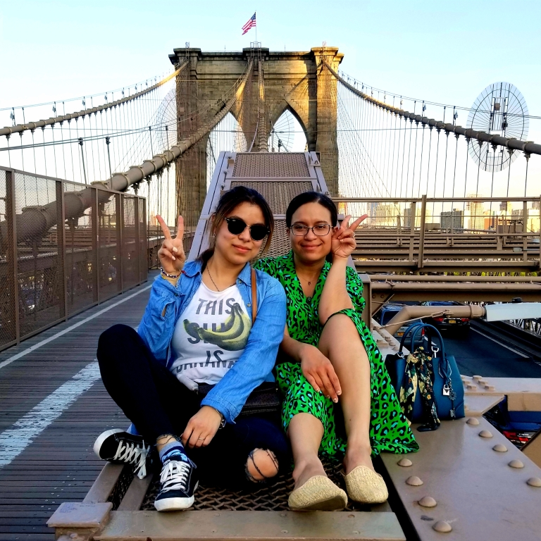 Two brunettes flash peace signs sitting on the Brooklyn Bridge.