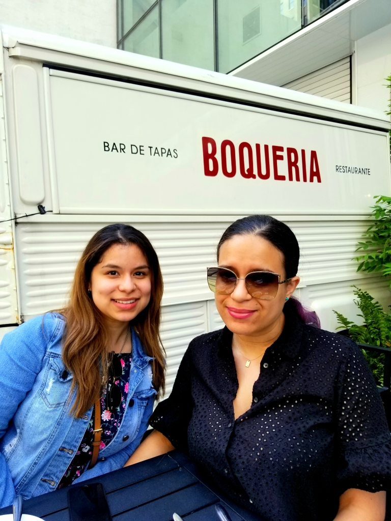 Two brunettes smile, a white truck behind them reading