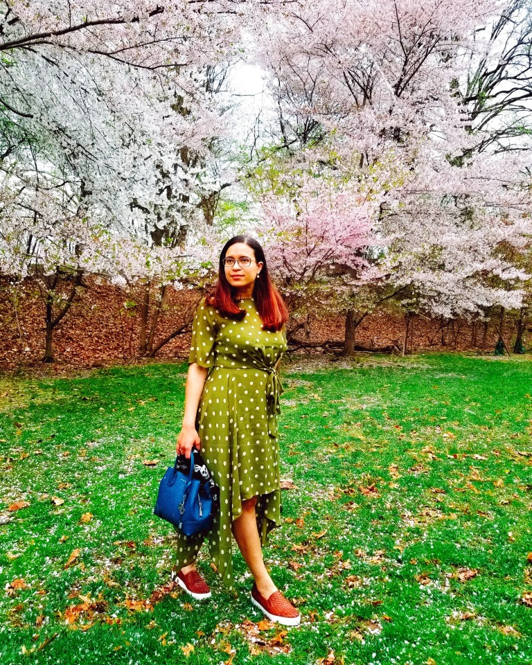 Brunette poses with teal handbag in cherry blossom grove.