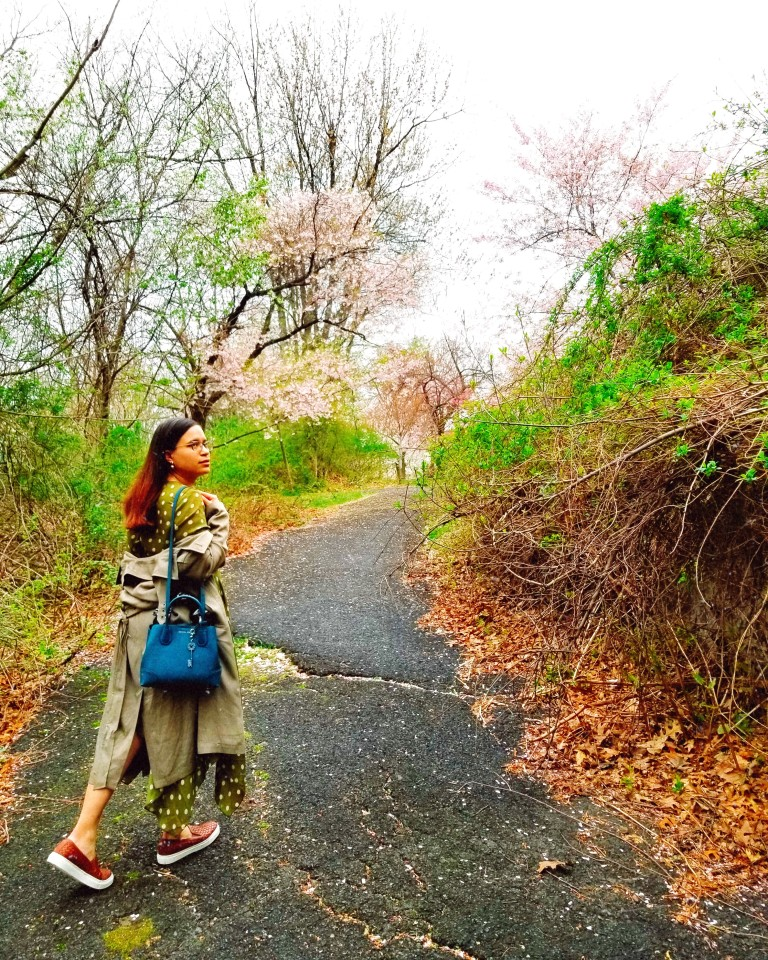 Brunette woman treads a paved florid path.