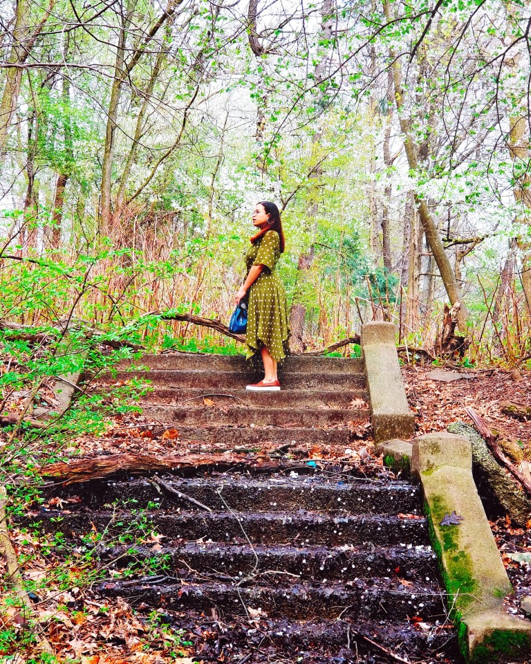 Brunette stands atop muddy stone stairs.