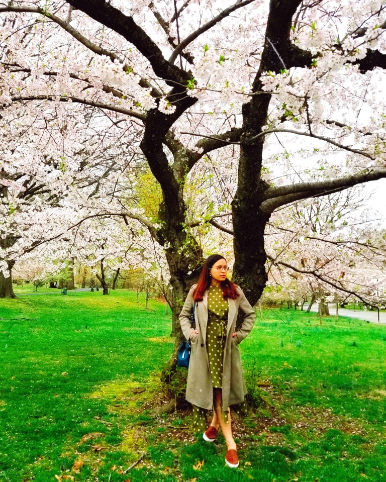 Brunette tucks hands in trench coat pockets in front of cherry blossom tree.