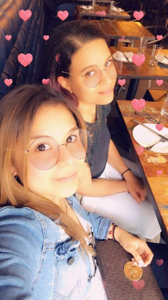 Two brunettes smile, round glasses and hearts filter overlaid on photo.