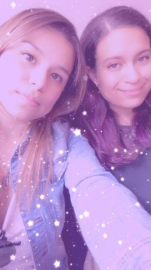 Two brunettes smile, a purple filter and stars overlaid on the photo.