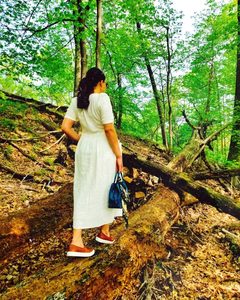 Brunette in white midi dress and cognac leather sneakers treads fallen, molding tree trunk.