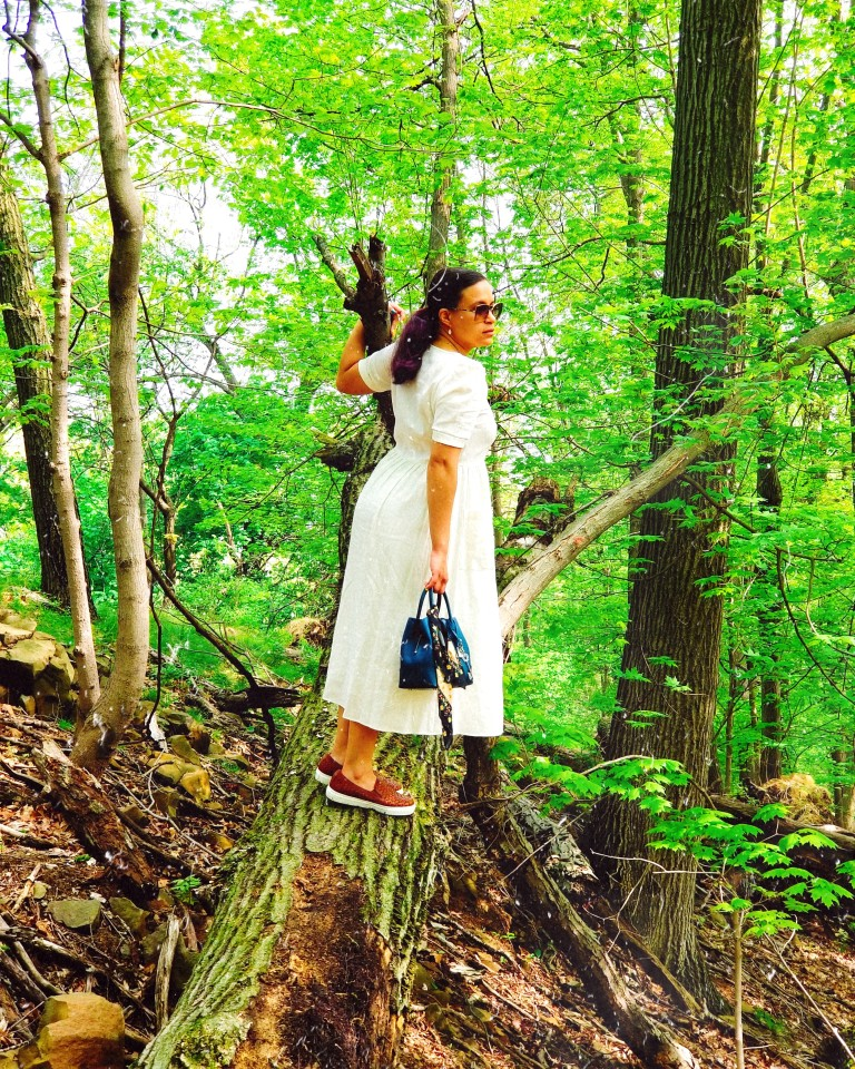 Brunette in white midi dress and cognac leather sneakers leans forward on fallen tree trunk, steadying herself with one hand on branch.