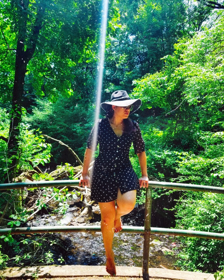Brunette sits on bridge railing wearing a little black polka-dot mini dress and charcoal gray sunhat.