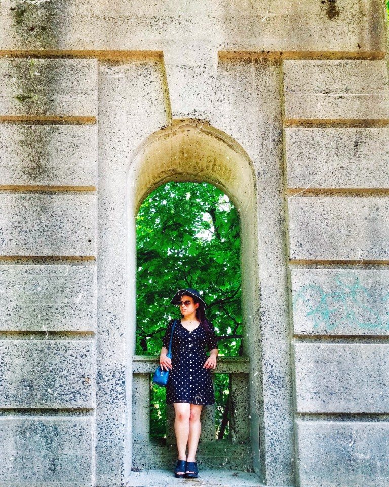 Brunette leans back in stone archway wearing a little black polka-dot mini dress and charcoal gray sunhat.