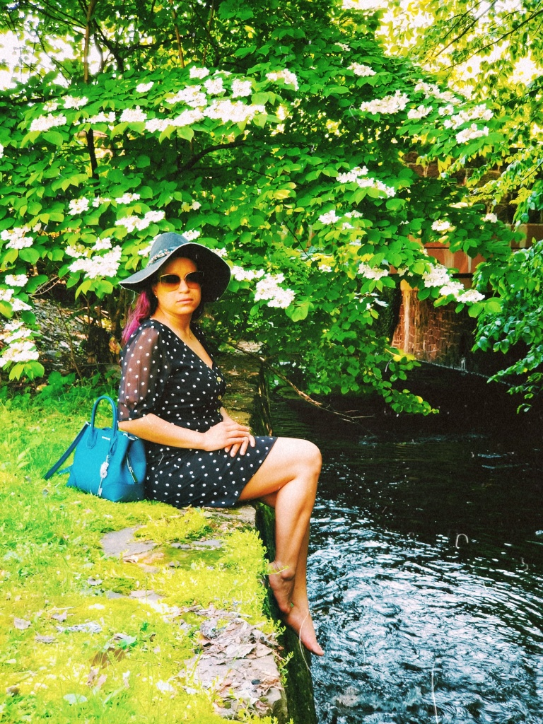 Brunette sits at the edge of a walled stream, teal handbag set down behind her.