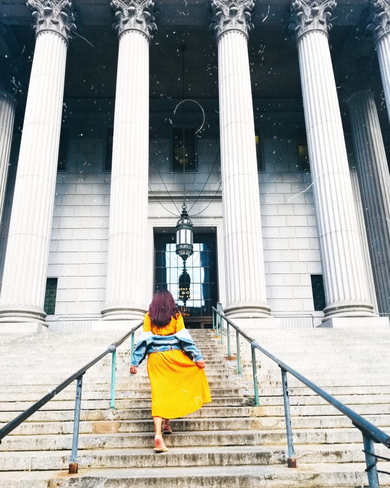Brunette in yellow midi dress and denim jacket climbs steps of New York County Supreme Court, tall white columns and blocks, a tiled glass door and black lantern suspended from black chains.