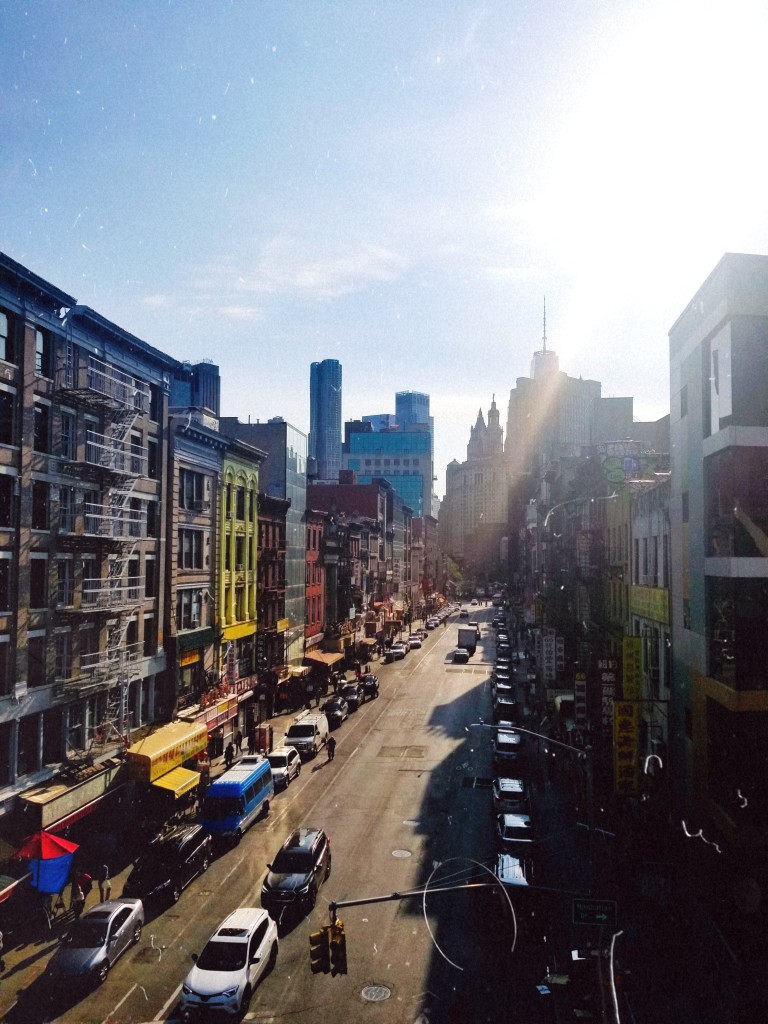 A view of Market Street, lined with colorful buildings, from the Manhattan Bridge Pedestrian Path.