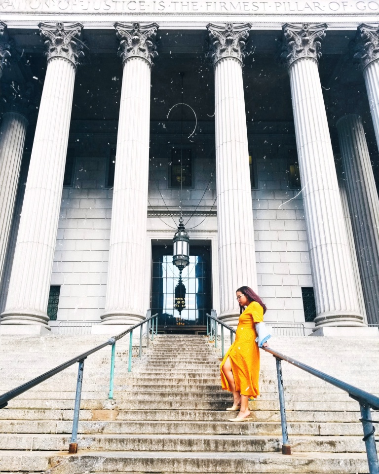 Brunette in yellow midi dress and denim jacket leans against railing at New York County Supreme Court, tall white columns and blocks, a tiled glass door and black lantern suspended from black chains.