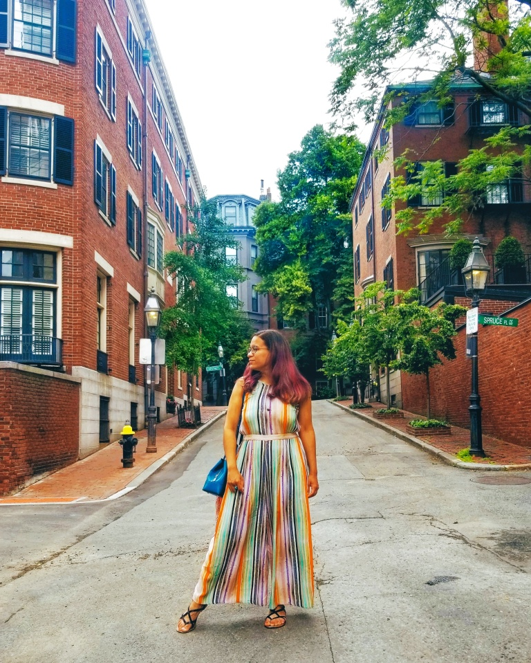 Brunette in colorful striped jumpsuit looks off to side, tree-lined street of brick row houses behind her.