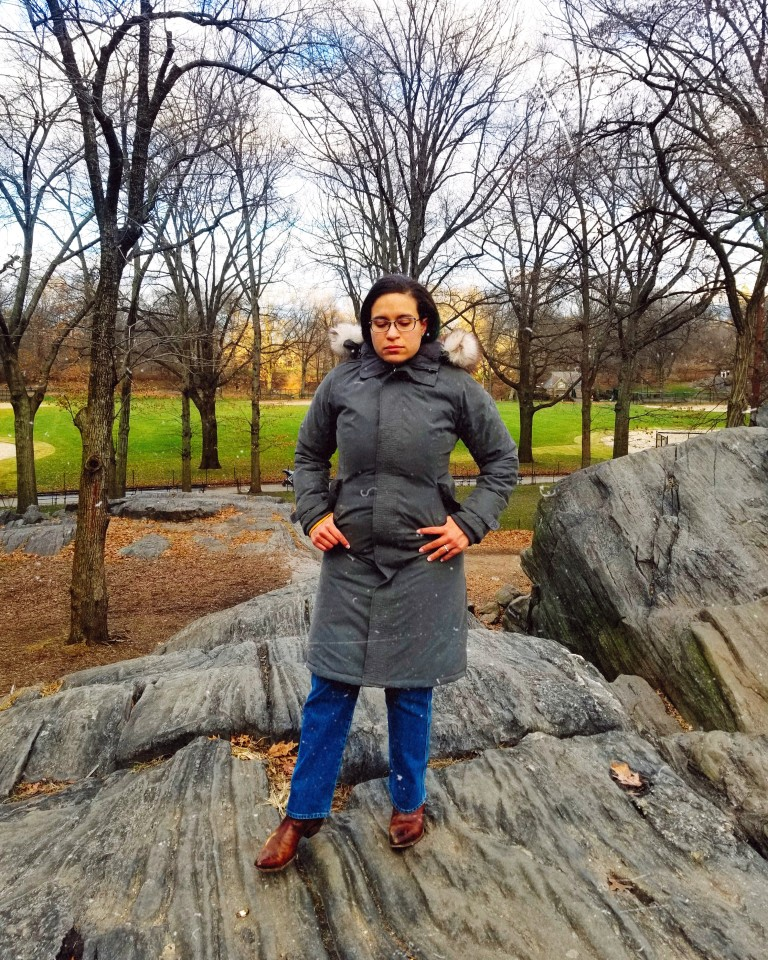 Brunette in a zipped-up gray parka stands on rock formation overlooking baseball field in Central Park.