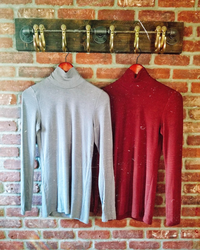 Two fitted turtleneck sweaters hang from rustic hooks against brick backdrop.